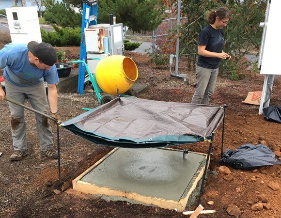 Pacific Northwest Seismic Network (PSNS) engineers have poured the concrete pad for the strong-motion instrument and are working on installing equipment at P376 in Salem, Oregon. (Photo/Sara Meyer, PNSN)