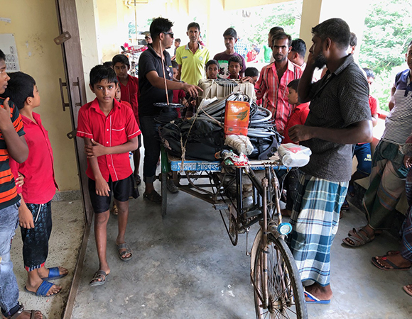 Sanju Singha (center with sunglasses) unloads a tricycle rickshaw (a very common form of local land transport in the delta) of equipment brought from the cargo boat one kilometer away to the Baintala Primary School. Most rickshaws are now battery operated—a recent technological advancement. (Photo/John Galetzka, UNAVCO)