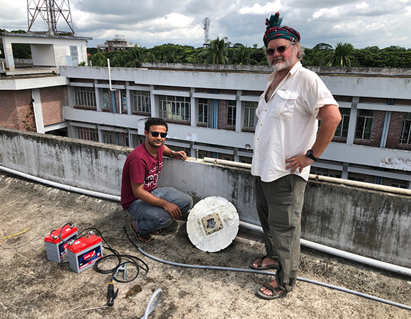 Hasnat Jaman (Barisal University) and Chris Small (Lamont-Doherty Earth Observatory) remove an old, damaged GPS antenna and prepare for some battery welding on the PUST monument at Patuakhali University. (Photo/John Galetzka, UNAVCO)
