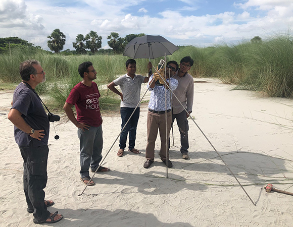 Mike Steckler (left), Hasnat Jaman (maroon shirt) and Sanju Singha (right) look on as Alamgir Hosain learns how to install a braced geodetic monument on the campus of Barisal University. (Photo/John Galetzka, UNAVCO)