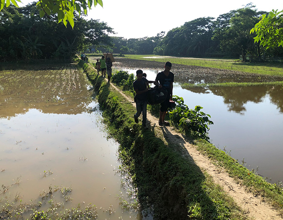 Villagers from Sonatola help the team move equipment from the charter boat several hundred meters across their polder to the proposed GNSS station and RSET sites. The rice paddies inside this polder are currently below high tide level. (Photo/John Galetzka, UNAVCO)
