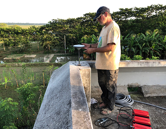 Mike Steckler installing the GNSS antenna on the SNT1 monument atop Sonatola Primary School. (Photo/John Galetzka, UNAVCO)