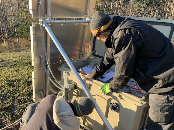 John Soderquist (IRIS) and Ken Austin (UNAVCO) finishing the external wiring for the GNSS antenna cable into the new enclosure. (Photo/J. Miner, IRIS)