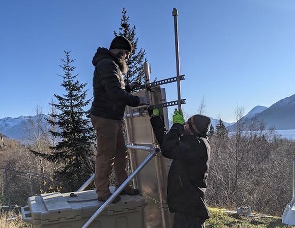 John Soderquist (IRIS) and Jeremy Miner (IRIS) installing the meteorological instrument on the new solar swing set. (Photo/K. Austin, UNAVCO)