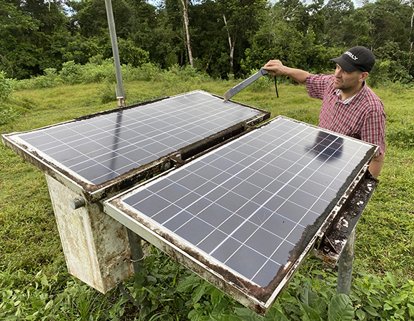 UNAVCO project manager Jim Normandeau cleans solar panels at station VERA. (Photo/Nicolas Bayou, UNAVCO)