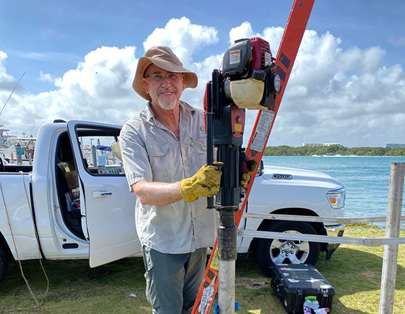 Shimon Wdowinski (PI, Florida International University) helping to install the stainless steel solar panel and equipment enclosure masts at the Haulover County Park site. (Photo/John Galetzka, UNAVCO)