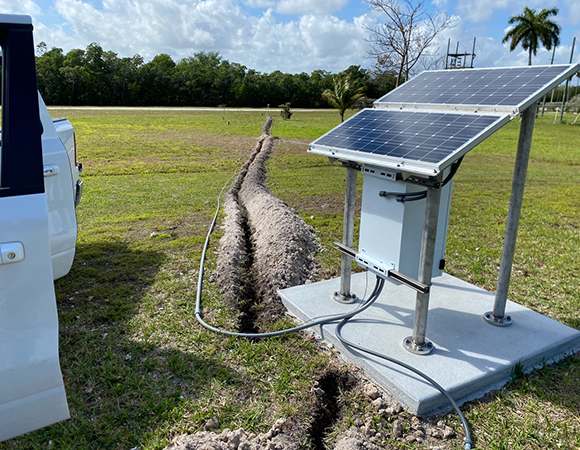 Completed 70-meter trench for GNSS antenna coaxial cable between the solar power and equipment enclosure assembly (foreground) and FCI2 monument (background) at FIU\'s Biscayne Bay Campus. (Photo/John Galetzka, UNAVCO)