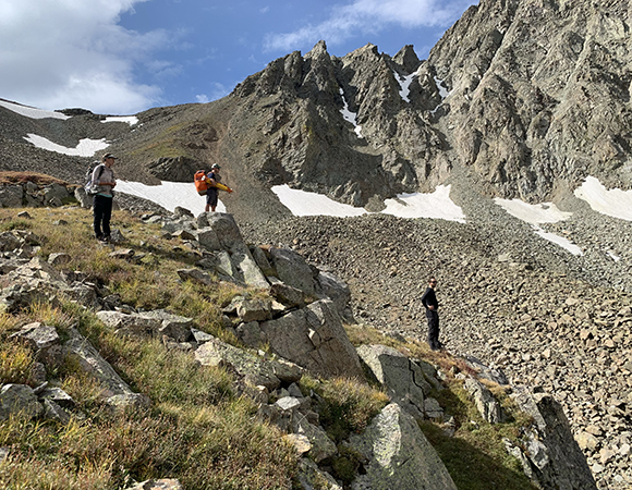 PI Dan McGrath, Bri Rick, and Spencer Niebuhr look out over the rock glacier deciding where to set up the TLS for best coverage. (Photo/Keith Williams, UNAVCO)