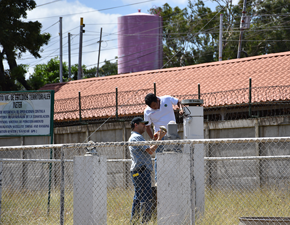 Elvis Leif Mendoza Rivera (INETER) and Jim Normandeau (UNAVCO) replace the chokering antenna's LNA at the cGPS station MANA, in Managua. (Photo/Pete LaFemina, Penn State)