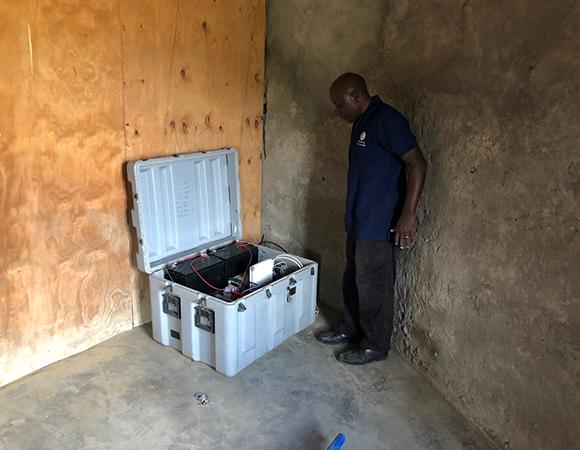Kristof Nkembo doing final inspection of the consolidated GNSS and satellite communication equipment enclosure at the network hub near Engaresero, Tanzania. (Photo/John Galetzka, UNAVCO)