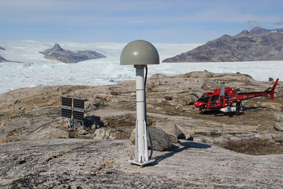 Photograph of GPS/GNSS site, TREO (Trefoldigheden) near Sermersooq, Greenland showing the antenna in the foreground with the receiver in an instrument enclosure behind solar panels in the background (left). Credit: Thomas Nylen, UNAVCO.