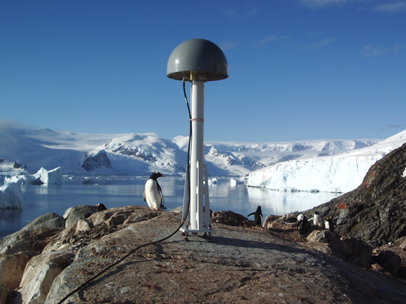 GPS antenna with penguins at Duthiers Point (DUPT), Antarctic Peninsula. Credit: UNAVCO