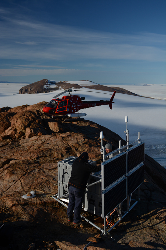 View of instrument box and solar panels for GPS station LBIB in Greenland National Park in northeast Greenland. Finn Bo Madsen (Technical University of Denmark) and Inge Fast (field support pilot) are shown working on the station. Photo taken by Thomas Nylen/UNAVCO.