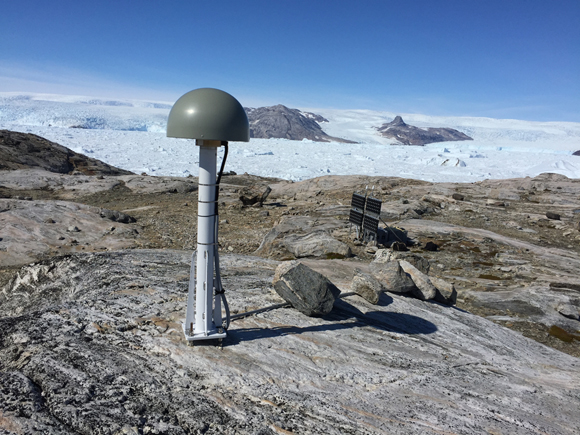 View of the antenna for GPS station Trefoldighedens (TREO) and instrument box behind solar panels in southeast Greenland. Photo taken by Thomas Nylen/UNAVCO.