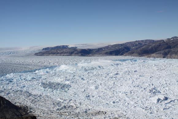Photograph of a calving event in progress at the marine terminus of Helheim Glacier, Greenland. Photo taken by Tavi Murray.