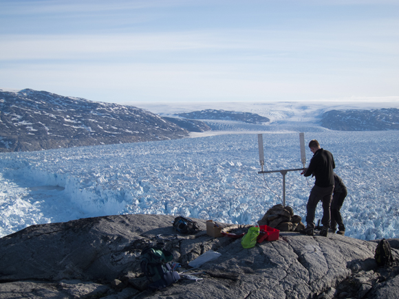 Setting up instruments for observations with view of Helheim Glacier, Greenland in the background. Photo taken by Tavi Murray.