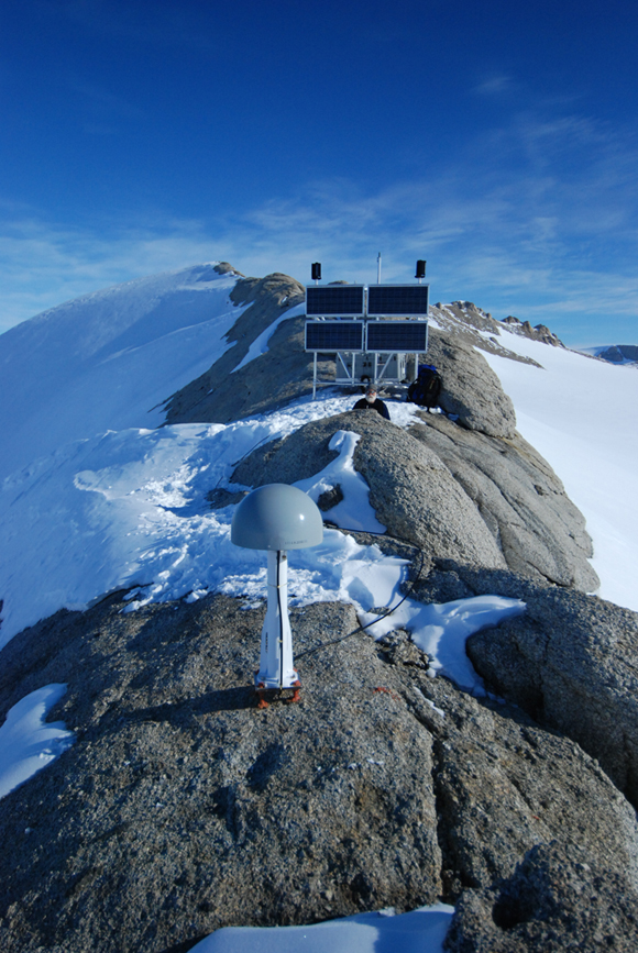 Photograph of GPS station SUGG at Mt. Sugg. Antenna in the foreground with instrument box, power {e.g. solar panels when there is sun and wind turbines (black cylinders mounted on solar panels) when there is no sun} and communications in the background. Researcher Donald Voight is in the middle ground. Photograph courtesy of UNAVCO.