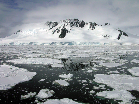 Sailing through the Neumayer Channel along the Antarctic Peninsula, aboard the Research Vessel Laurence M.Gould, heading to Palmer Station. Photograph of mountains, ice and ocean converging in Antarctica. Photograph courtesy of Joseph Pettit/UNAVCO.