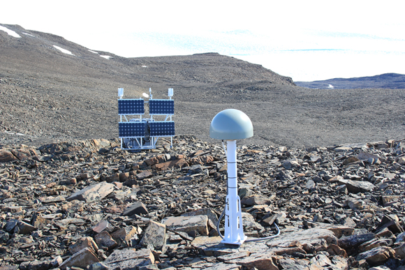 View of antenna protected in a radome (foreground) with solar panels, wind turbines, batteries, GNSS receiver and electronics (background) for GNET GNSS site, RINK. Photograph courtesy of UNAVCO.