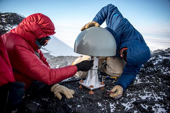 Inspecting the GPS antenna at Toney Mountain, Marie Byrd Land, Antarctica (Site TOMO). January 13, 2018 (Photo/Nicolas Bayou, UNAVCO).