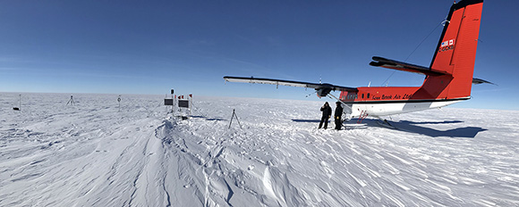 View of GPS site on the Whillans Ice Streams in Antarctica. Solar panels and black wind turbines provide energy to run the site 24/7 all year long. Photograph courtesy of Matthew Siegfried.