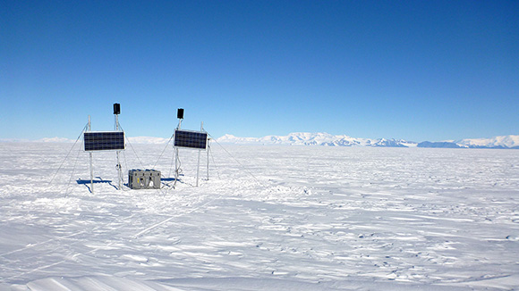 View of GPS site on the Whillans Ice Streams in Antarctica. Solar panels and black wind turbines provide energy to run the site 24/7 all year long. White GPS antenna behind the panels on the right and instruments in the gray box in the middle. Photograph courtesy of Matthew Siegfried.
