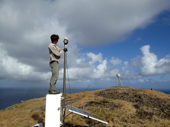 UNAVCO field engineer Jacob Sklar installs a meteorological instrument on the enclosure post of GPS COCONet site, CN47 on Saint Lucia Island in the Caribbean. Radome covering the tripod-mounted GPS antenna in the background. COCONet is a network of GPS and MET observations in the Caribbean and parts of Central America that can help with earthquake and tsunami early warning. Photograph by Mike Fend/UNAVCO.