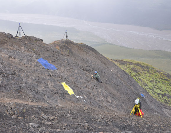 Dinosaur tracksite in Denali National Park and Preserve with researcher studying a print in midst of terrestrial laser scanner set-up (scanner in lower right and reference targets on ridge top) and rubber molds (blue and yellow areas). Photograph courtesy of the Perot Museum of Nature and Science.