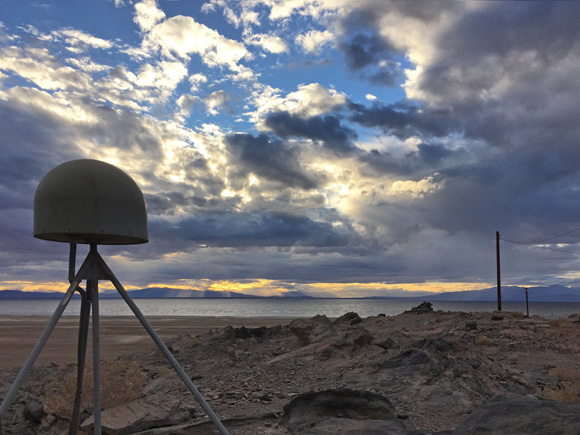 View of GPS station antenna for Plate Boundary Observatory site P507 with the Salton Sea in southern California in the background. Photo taken by Christian Walls/UNAVCO.