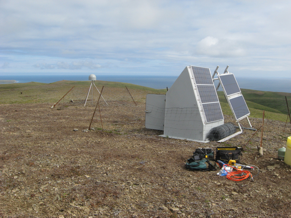 GPS Station AC13 on Chirikof Island, Alaska. AC13 is part of EarthScope\'s Plate Boundary Observatory (PBO), maintained by UNAVCO and supported by the National Science Foundation. Observations at the site suggest the fault beneath the station is locked. Figure courtesy of UNAVCO.