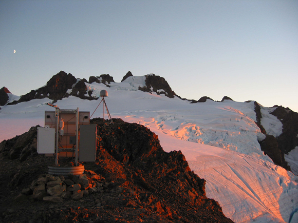 View of GPS site SC03 [part of the Plate Boundary Observatory (PBO) and the Pacific Northwest Geodetic Network (PANGA)], on Mt. Olympus in the Olympic National Park, Washington. Site includes antenna (baffled on tripod in the background), instrument box for GPS receiver and other electronics, power supplies (batteries and solar panels), meteorological instrument, and communications. Photograph by Ellie Boyce/UNAVCO.