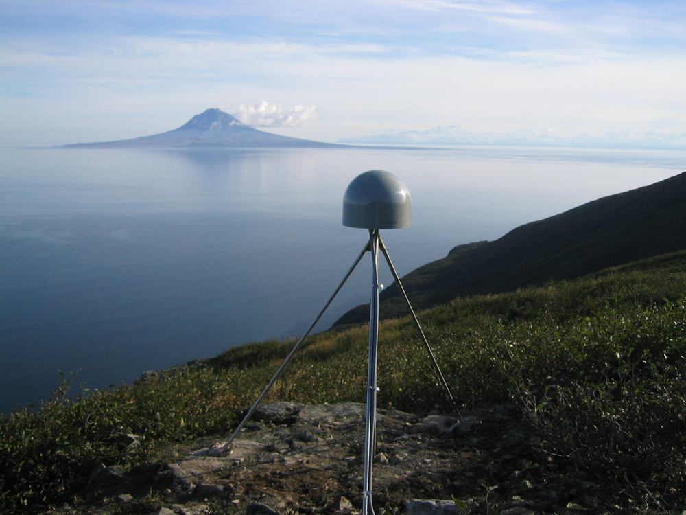 Plate Boundary Observatory GPS/GNSS site, AC59. The site is located at Ursus Head, Alaska. The photograph shows the antenna covered in a radome and securely mounted with a 3-point brace. In the background is Mt Augustine Volcano. AC59 is closest to the epicenter of the Iniskin earthquake and is a focal point of the different GPS/GNSS baselines used in this study. Credit: UNAVCO