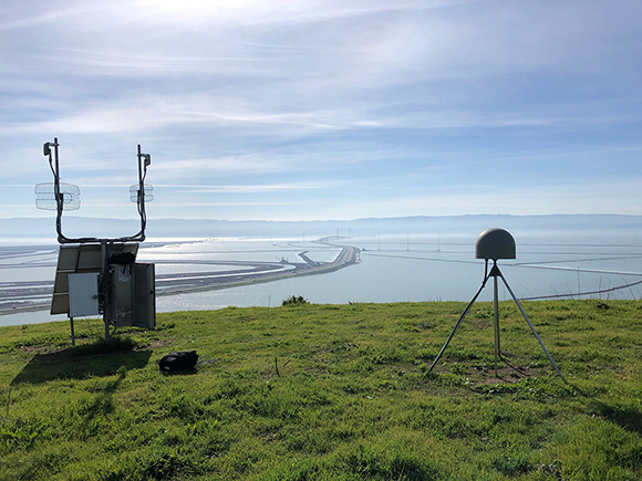 Photograph of the Plate Boundary Observatory site P222, a ShakeAlert component located in the Bay Area. The site is called CoyoteHillsCN2005 and is located near Fremont, California. The antenna is to the right, covered by a radome and stably mounted on a three brace system. To the left, is the instrument enclosure with the GNSS receiver plus power and communications. The photograph was taken by Ryan Turner on January 31, 2018, credit UNAVCO.