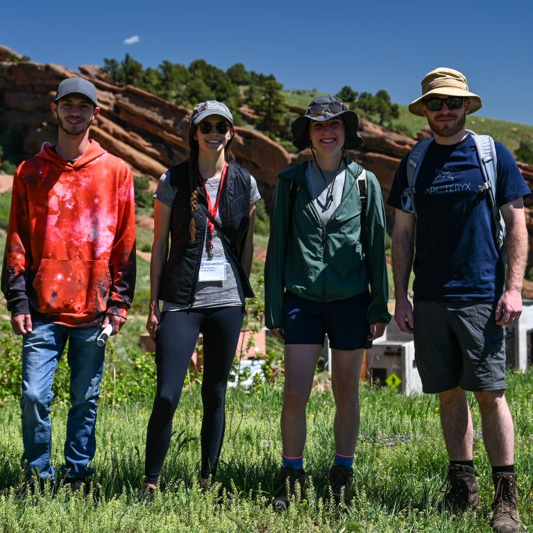 The four 2021 Geo-Launchpad interns standing in a line in front of a large outcrop at Red Rocks Park in Morrison, CO.