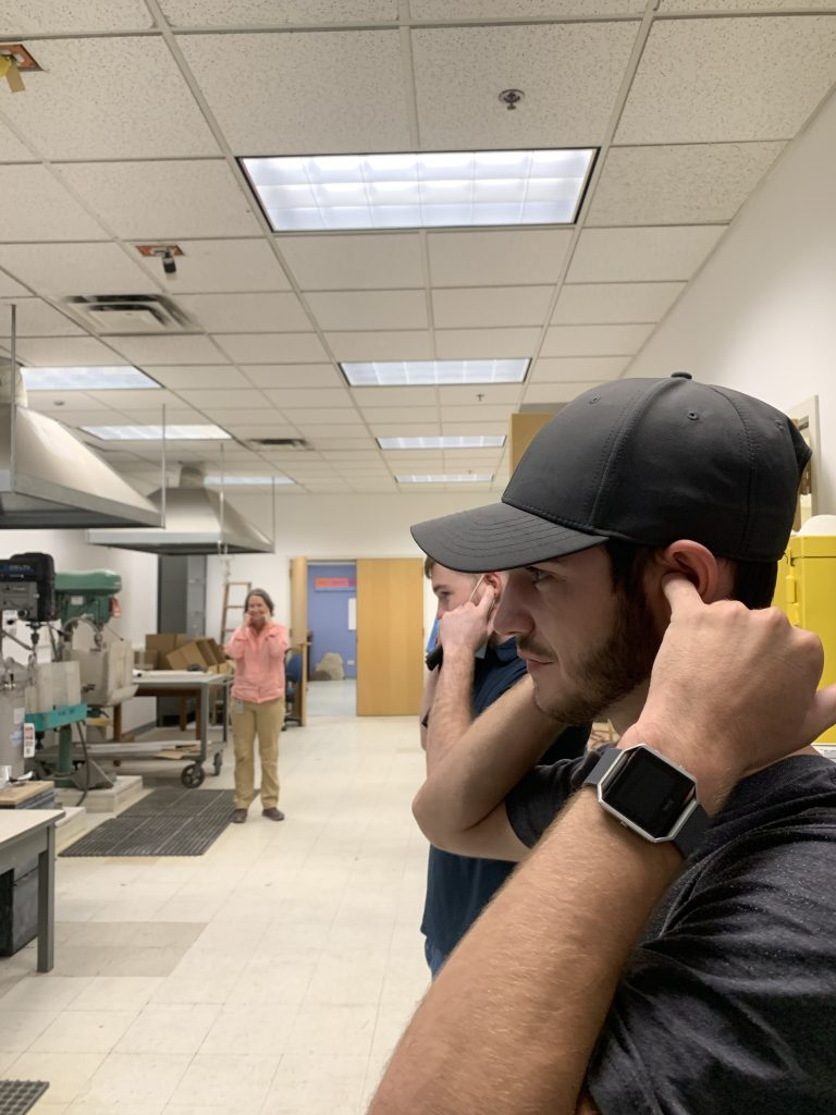 Geo-Launchpad intern Jimmy Swift plugging his ears while an employee cuts a sample of granite.