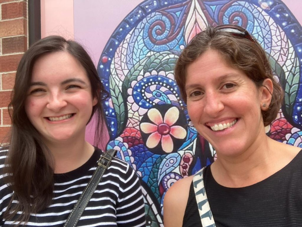 Samantha Motz and Dr. Kamini Singha smiling in front of a mural.
