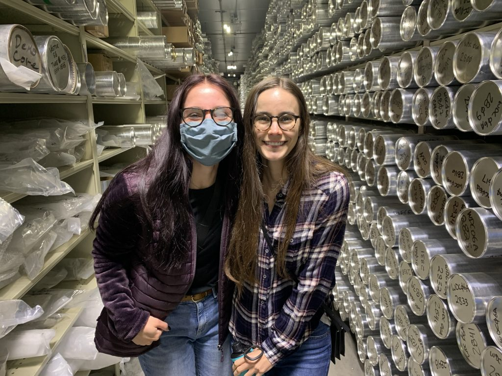 Geo-Launchpad interns Madalyn Massey and Allison Sowers smiling in front of rows of ice cores.