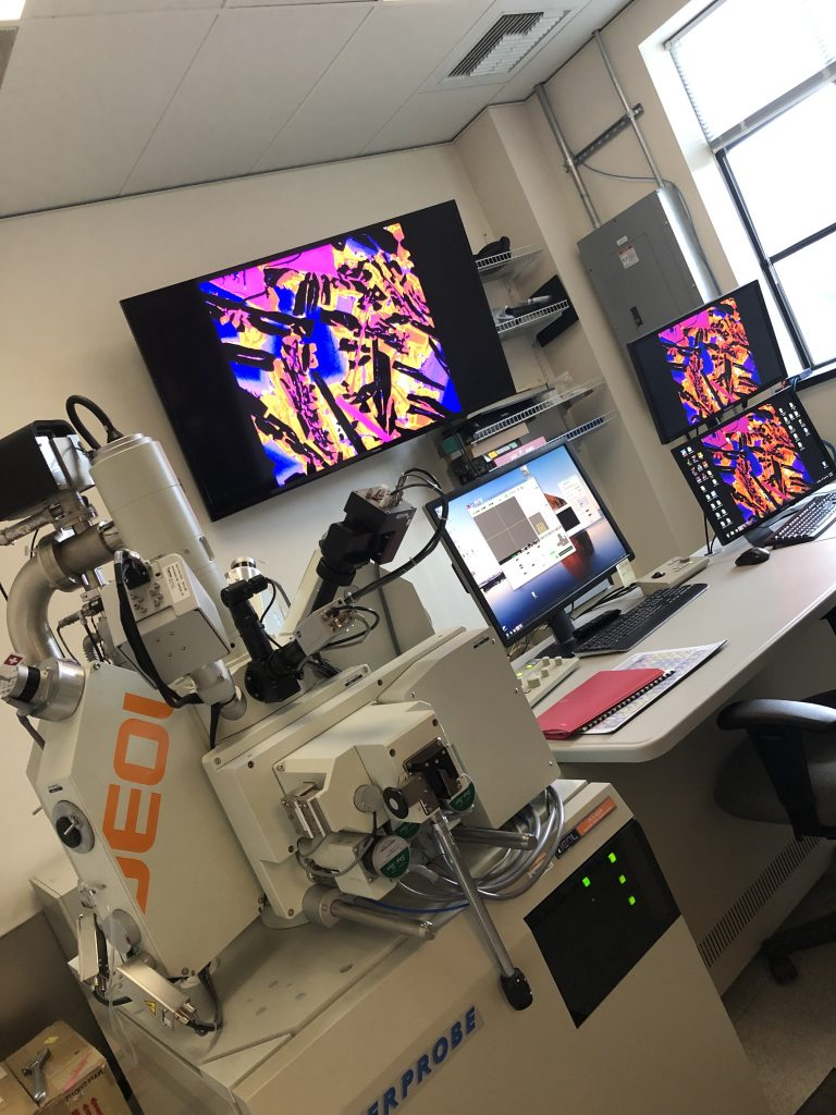 The electron microprobe is located to the left, and there are many screens with the colorful thin section displayed.