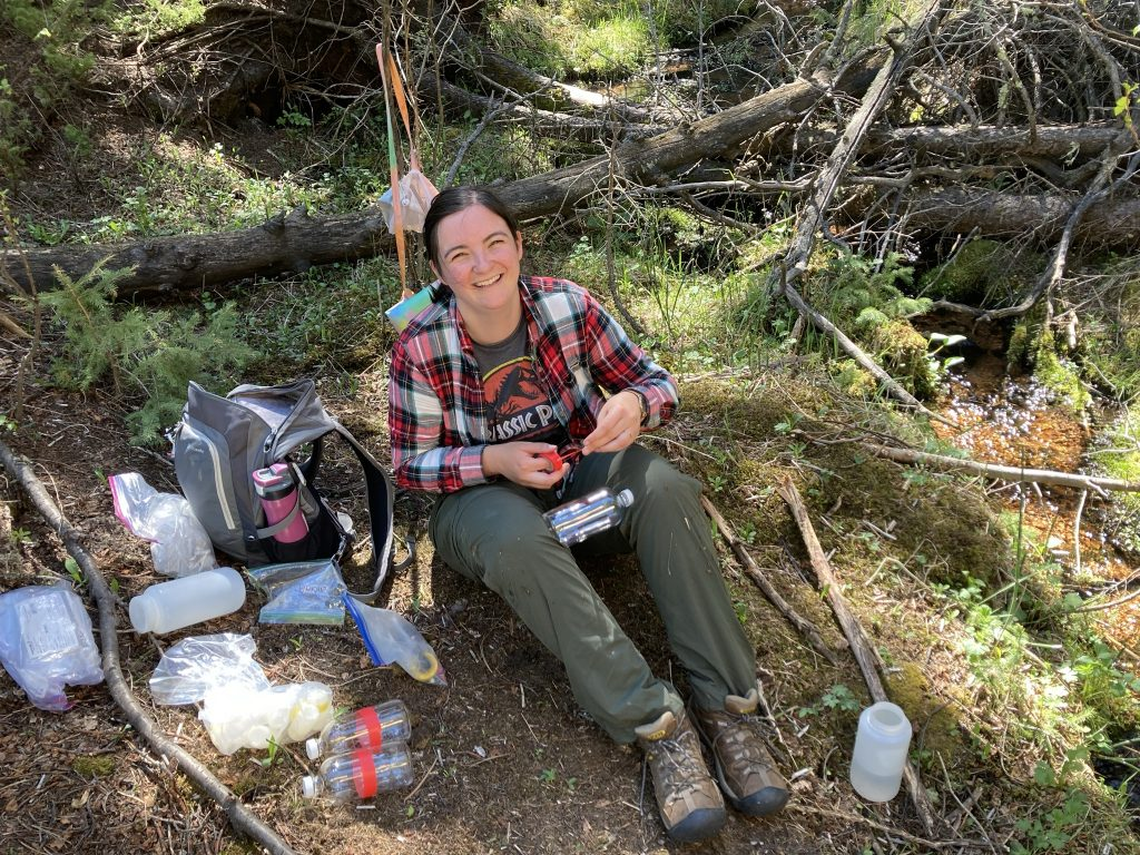 Samantha Motz sitting in the shade of a tree, labeling a water bottle for sampling.