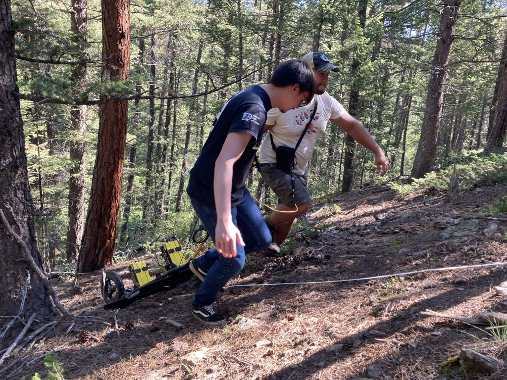 Alex Nguyen and another lab member pulling a GPR instrument up a hill in a forest