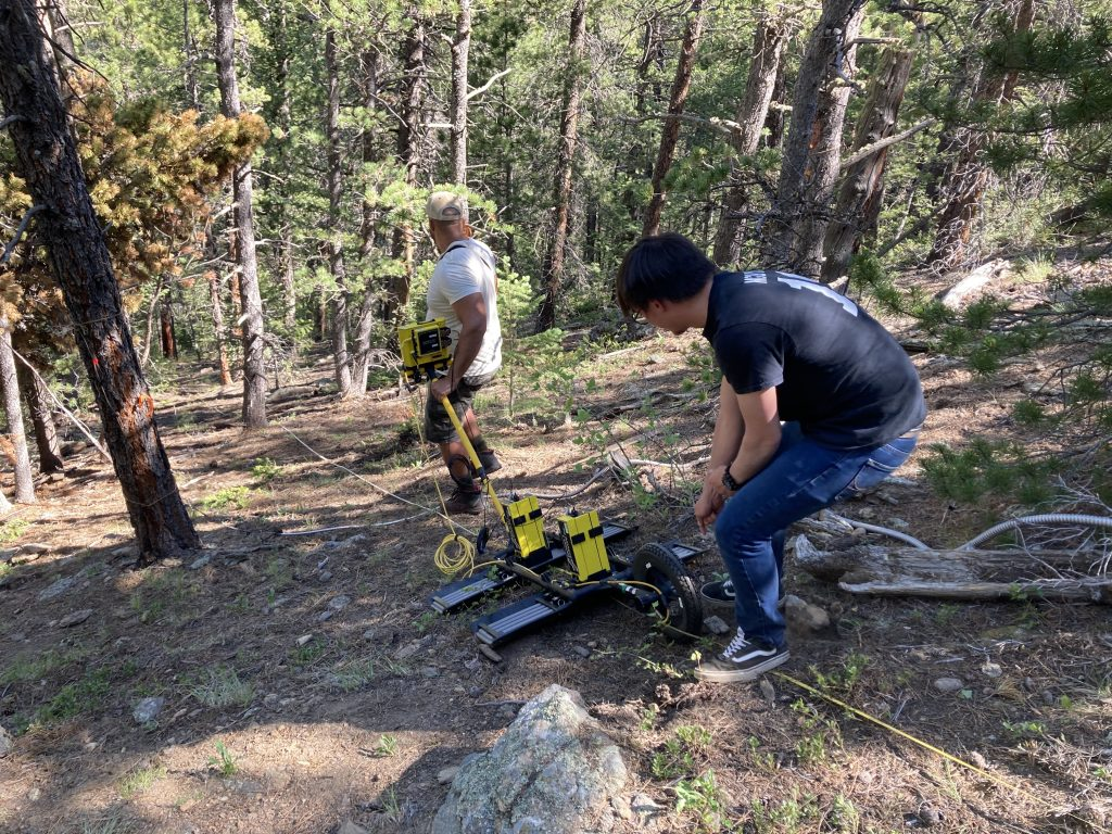 Alex pulling the GPR instrument uphill while another lab member pushes it at the same time.