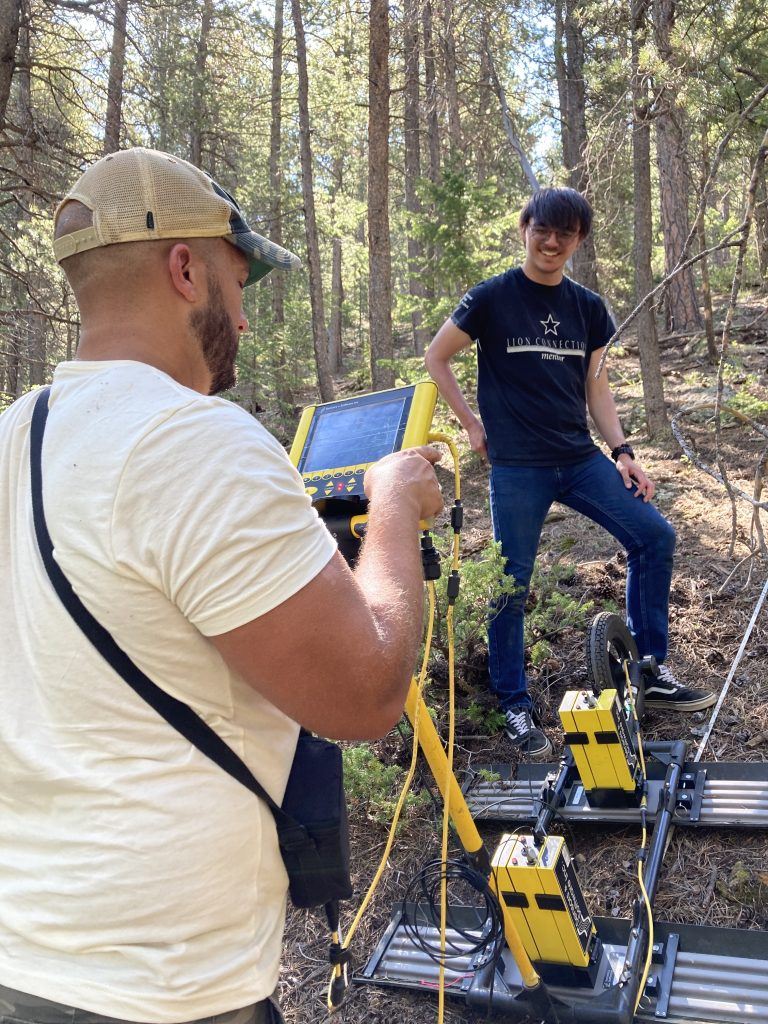 Alex Nguyen takes a break from pulling the GPR instrument while another lab member looks at the screen of the GPR instrument.