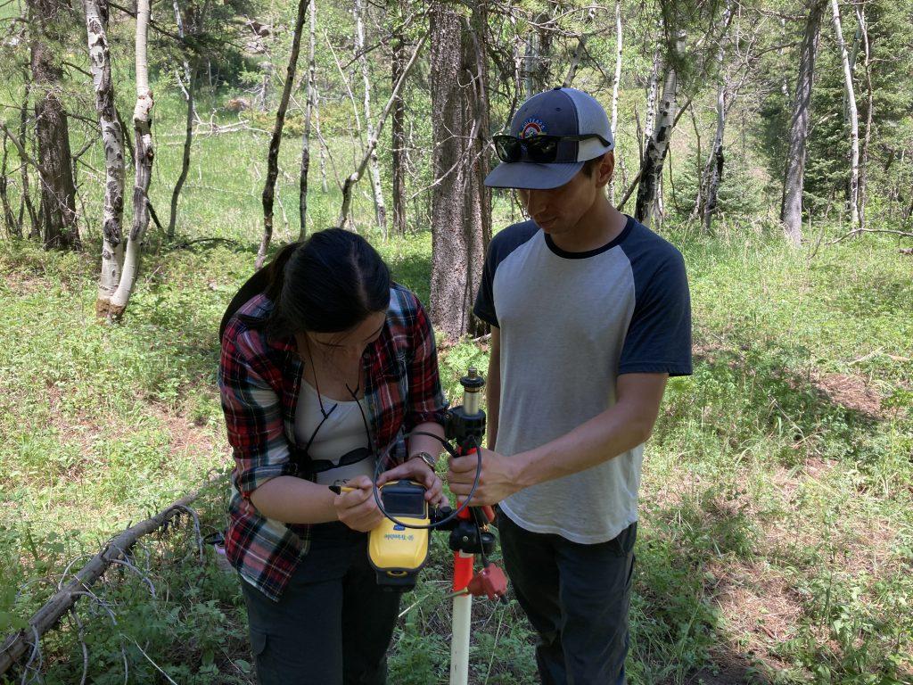 Samantha Motz and Kenny Swift Bird are examining a seismic instrument.