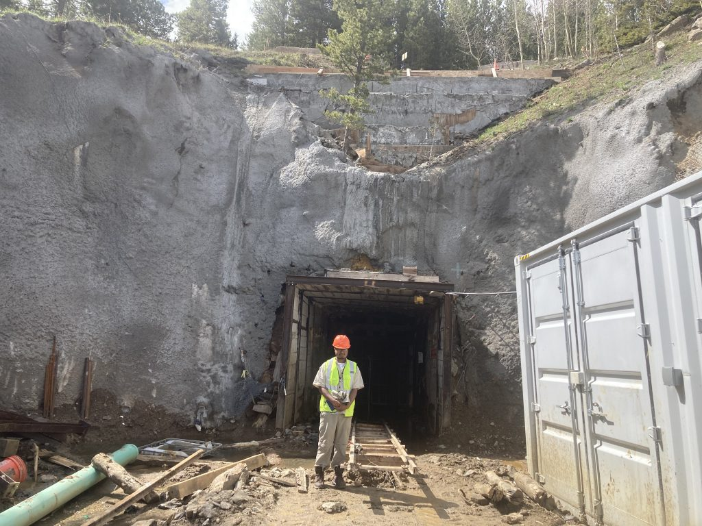 RESESS intern Shams Ahmed standing in front of a mine shaft at the Cross Mine, wearing a safety vest and hard hat.