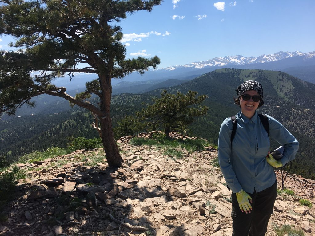 2021 RESESS Intern Shana Egan at the top of Sugarloaf Mountain in Colorado. There's a tree next to her and mountains visible in the background.