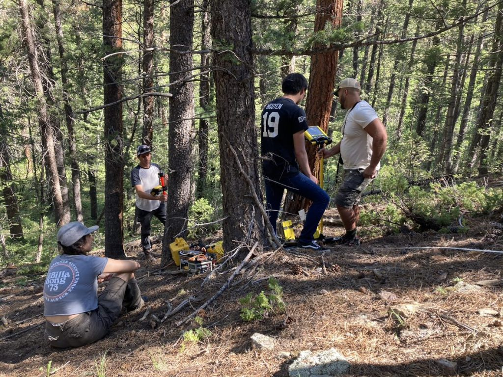 Four people work to pull a GPR instrument with a yellow robe up a hill in a forest