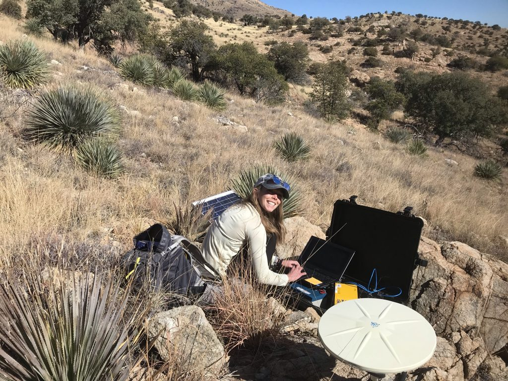 Cassie Hanagan crouching down to work with equipment in the field for her PhD.