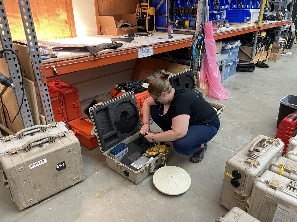 women kneeling to work on components in case