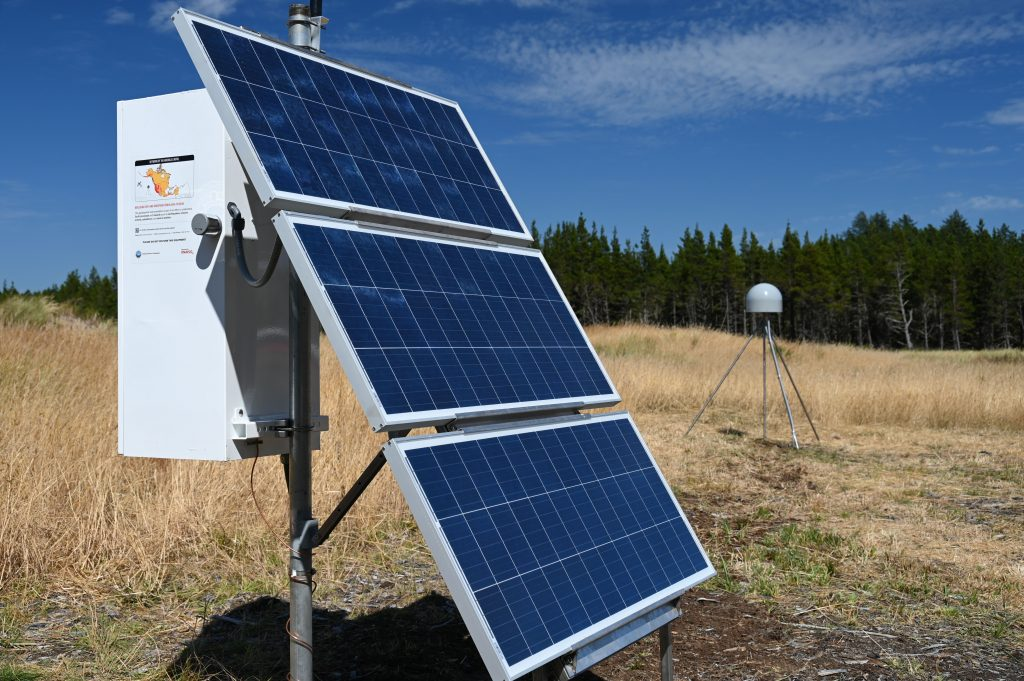 solar panels on enclosure box with antenna behind and trees in the background